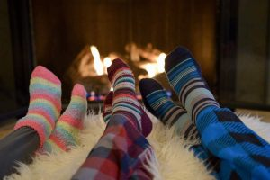 family in front of the fire wearing thermal socks